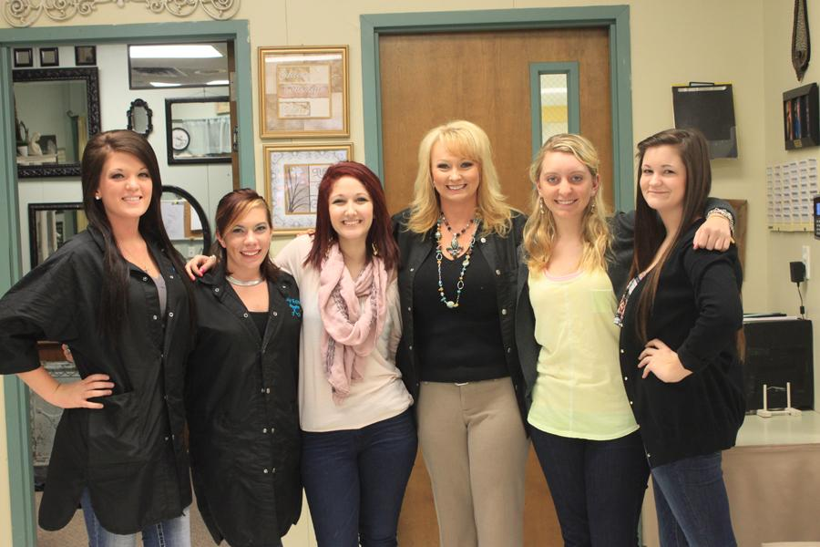 Kim+Levens+helps+her+senior+cosmetology+students+get+sized+for+their+uniforms.