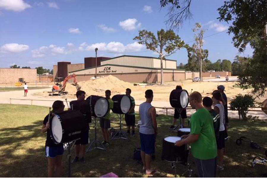 The Battlin' Bear Band drumline makes adjustments to their practice as they watch the nearby construction.