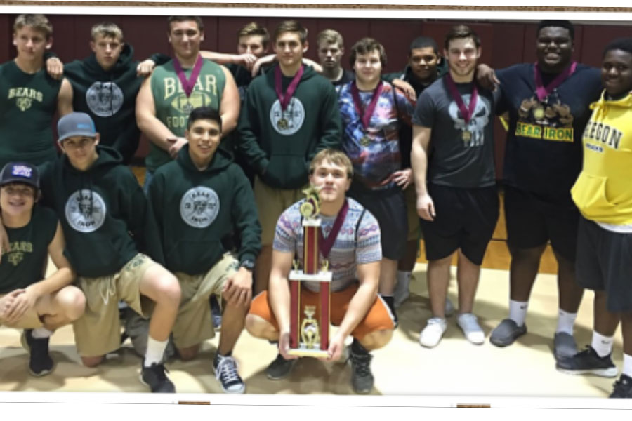 The boys powerlifting team proudly shows off its first place trophy from the Silsbee meet.