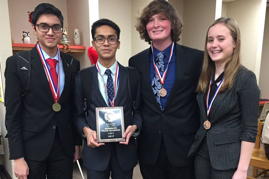 The+CX+Debate+Team+displays+their+district+champions+plaque.+