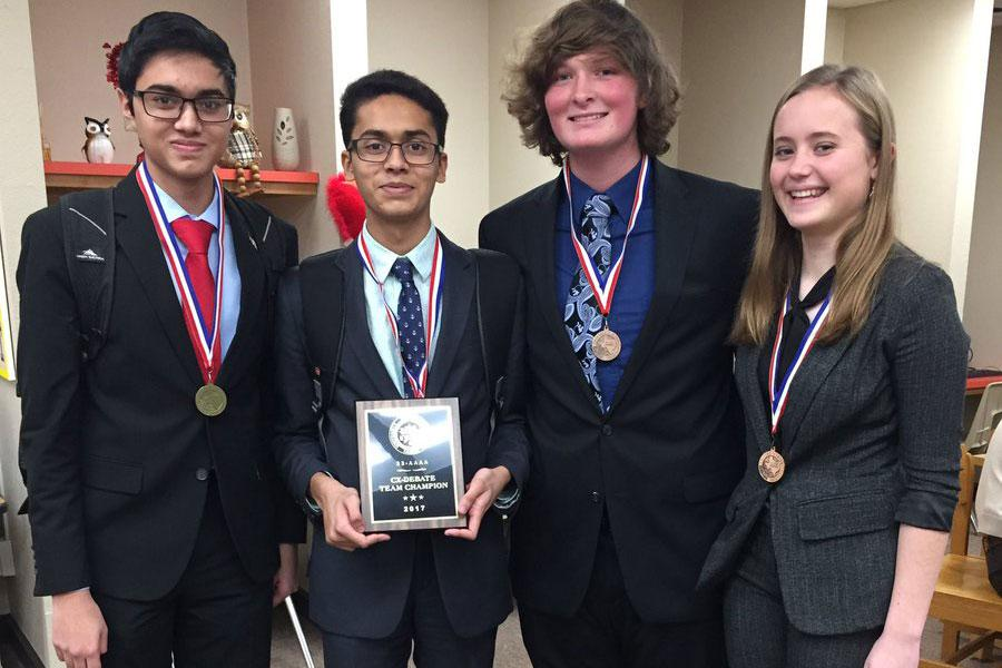 The CX Debate Team displays their district champions plaque.
