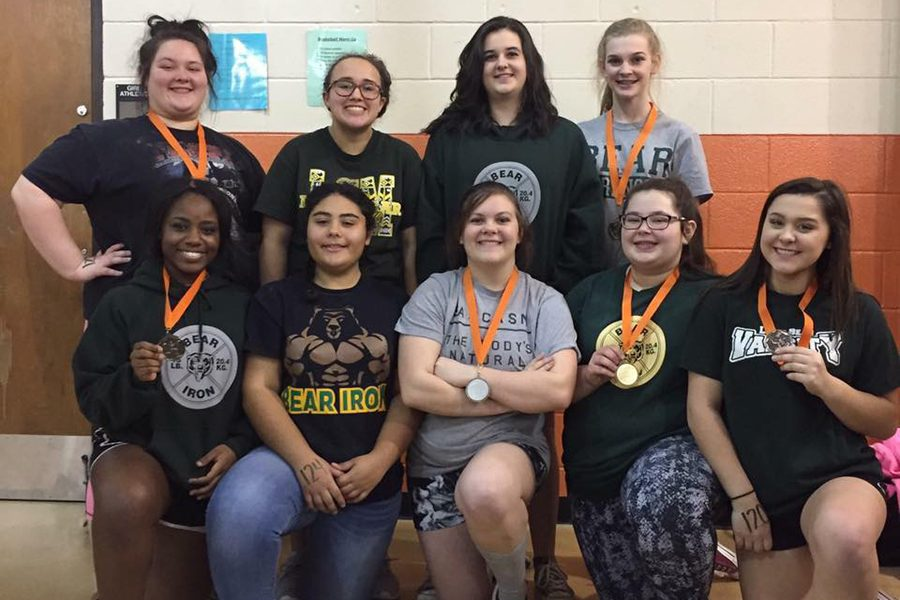 The+girls+powerlifting+team+shows+off+their+medals+at+the+Orangefield+meet.+