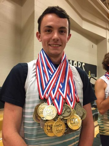 Senior Eli Peveto shows off his many medals from years of winning cross country meets.